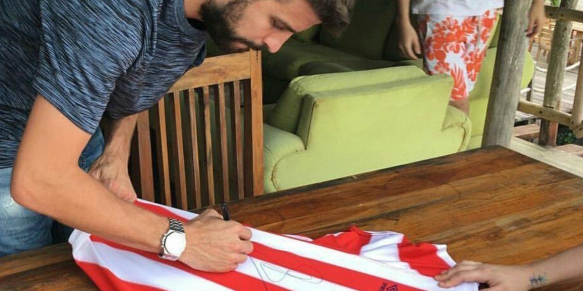 Gerard Piqué mientras firmaba una camiseta del Junior.
