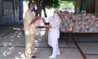 Funcionarias del PAE entregan los mercados a los padres de los estudiantes.