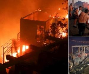 Varias personas intentan sofocar las llamas en sus viviendas que se han visto afectadas por un incendio forestal que alcanzó ayer en Valparaíso.