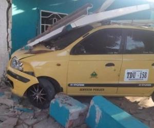 Así quedó el taxi tras estrellarse contra la vivienda.