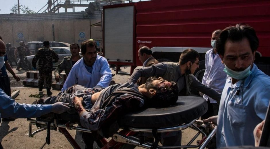 Un hombre herido es trasladado en camilla hacia la ambulancia