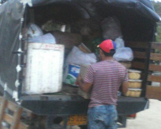 David Argüello (izq), coordinador de entregas de Nutrir Caribe, hace las descargas irregulares en los colegios.